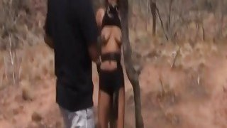 African slave gets tortured by two studs outdoors